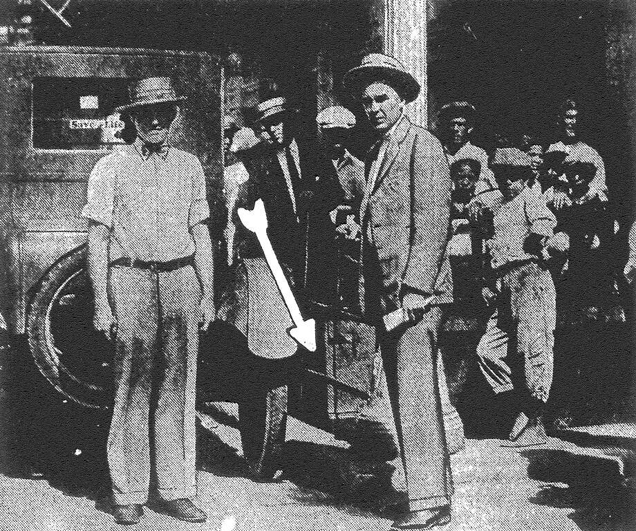 Above is pictured the scene of the daring Light payroll holdup and the two victims of the unidentified masked bandits. B.F. Farmer, cashier, is shown at right, and Gerald Myers is at the left. The arrow points to where one bandit met Farmer, thrust a pistol into his side and grabbed the money bag. He then stepped into a car with two confederates and fled. Published in the San Antonio Light June 26, 1928. Photo: File Photo