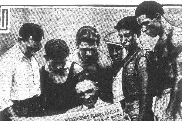 "The Light is delivered at the Business Men's A.C. Gym and the boys gather around to read ""The Assassin,"" the Stanley Ketchel serial, over the shoulder of Promoter Jack Shelton. Left to right, Nobe Cervantes, Hill Hernandez, Kid Gilbert, Rocky Kansas, Danny Perez and Kid Herrera. Published in the San Antonio Light June 18, 1928."