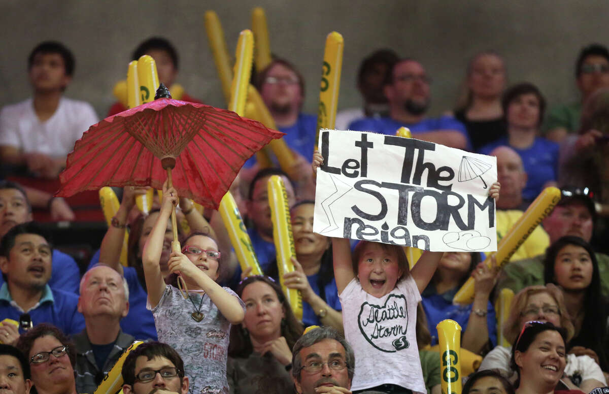 Young Seattle Storm fans cheer the team against the Phoenix Mercury during the Seattle Storm home opener on Sunday, June 2, 2013 at KeyArena in Seattle.
