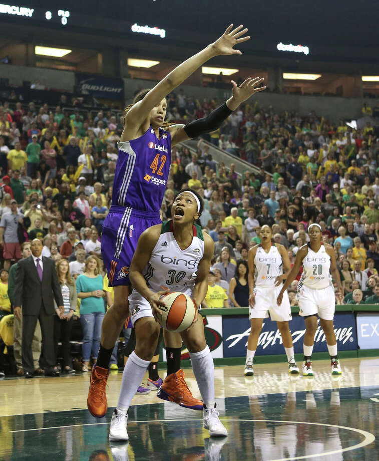 Seattle Storm player Tanisha Wright works her way to the basket under Phoenix Mercury player Brittney Griner during the Seattle Storm home opener on Sunday, June 2, 2013 at KeyArena in Seattle. Photo: JOSHUA TRUJILLO, SEATTLEPI.COM / SEATTLEPI.COM