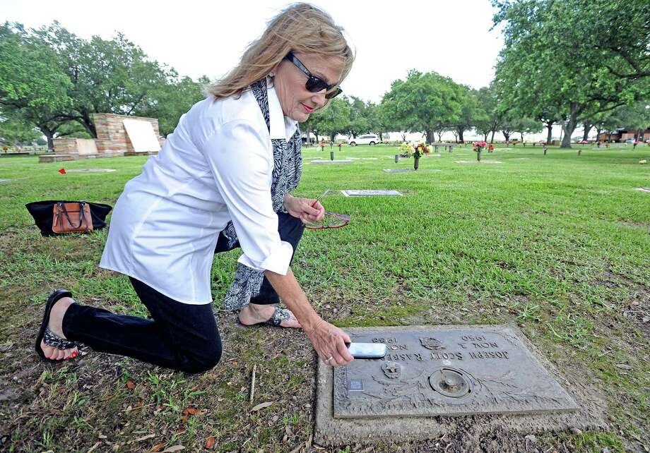 Cathy Shoemaker demonstrates how the Life Marker chip works by scanning a QR code on a headstone.  Photo taken: Randy Edwards/The Enterprise Photo: Randy Edwards