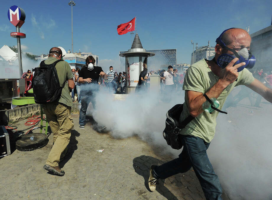 Turkish protestors run from tear gas as they take control of Taksim Square from security forces, after hours of street battles to protest at what they see as increasingly authoritarian rule on June 1, 2013 in Istanbul, Turkey. Initially a local protest over the fate of a park, it has broadened into anger over what are seen to be heavy-handed actions of Prime Minister Recep Tayyip Erdogan and his Islam-rooted AKP (Justice and Development Party) which includes new rules against consuming alcohol and tough police action against any opposition. Photo: Scott Peterson, Getty Images / 2013 Scott Peterson