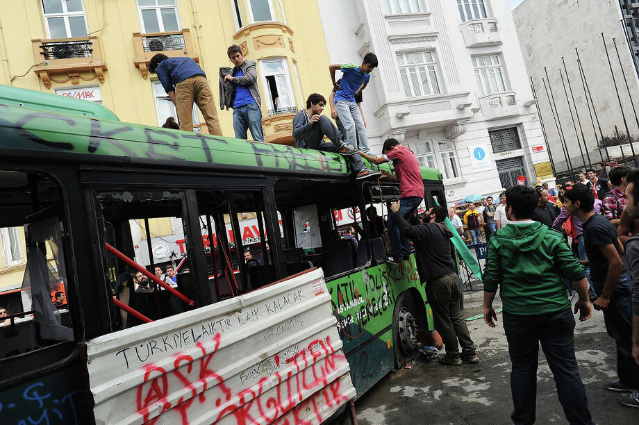 Young men scramble atop a wrecked bus as Turkish protestors celebrate their seizure from police of the central Taksim Square after two days of violent street battles in Istanbul, Turkey, on June 2, 2013. Initially a local protest over the fate of a park, it has broadened into anger over what are seen to be heavy-handed actions of Prime Minister Recep Tayyip Erdogan and his Islam-rooted AKP (Justice and Development Party) which includes new rules against consuming alcohol and tough police action against any opposition. Photo: Scott Peterson, Getty Images / 2013 Scott Peterson