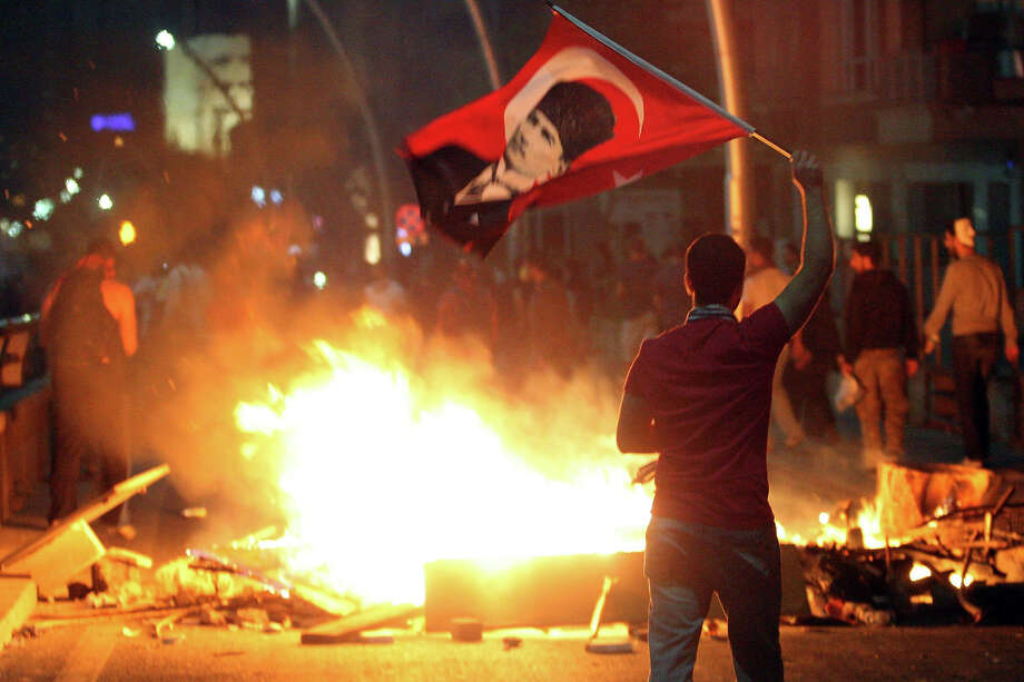An anti-government protester waves Turkey's national flag bearing a portrait of Mustafa Kemal Ataturk, founder of modern Turkey, during a demonstration, on June 2, 2013, in Ankara.  The unrest began as a local outcry against plans to redevelop Gezi Park, a rare green spot near Taksim, but after a heavy-handed police response the protests spread to other districts -- and then to dozens of cities across Turkey. Accused by critics of pushing an increasingly conservative and authoritarian agenda, Erdogan's government is facing the biggest protests since it took power in 2002. Photo: ADEM ALTAN, AFP/Getty Images / 2013 AFP