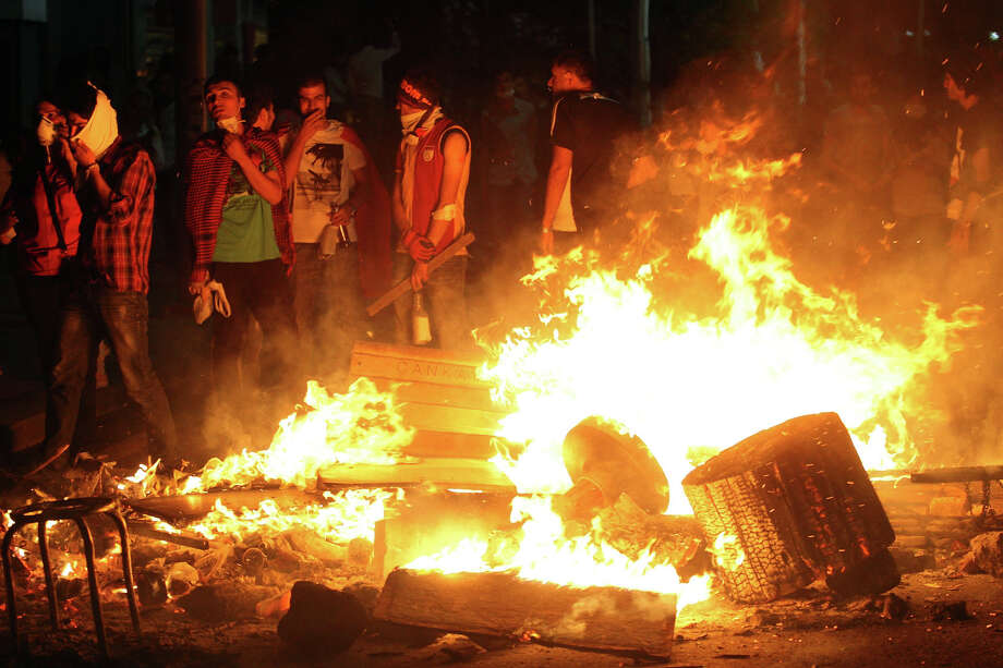 Protestors stand in front of items set on fire in Ankara, on June 3, 2013, in a nationwide wave of protests.Turkey's Islamist-rooted government faced growing pressure on June 3 after angry demonstrators clashed for a third night with police. The unrest began as a local outcry against plans to redevelop Gezi Park, a rare green spot near Taksim, but after a heavy-handed police response the protests spread to other districts -- and then to dozens of cities across Turkey. Accused by critics of pushing an increasingly conservative and authoritarian agenda, Erdogan's government is facing the biggest protests since it took power in 2002. Photo: ADEM ALTAN, AFP/Getty Images / 2013 AFP