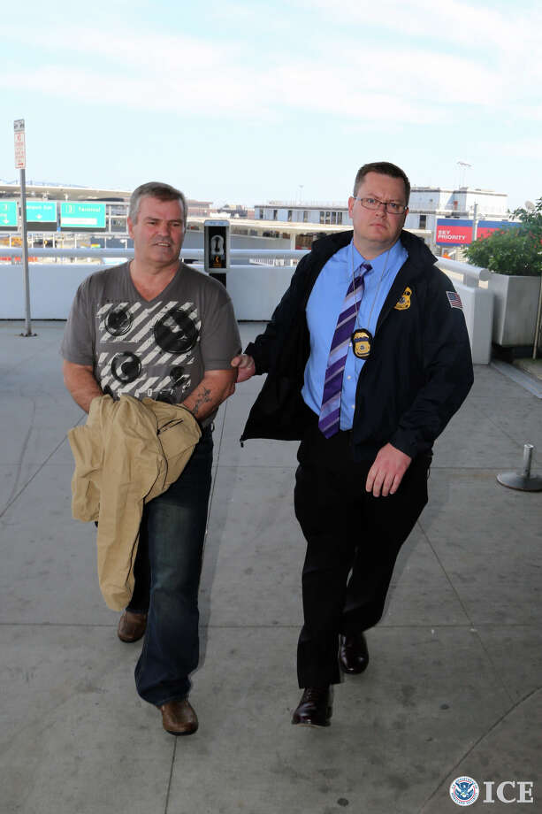 A federal agent escorts Sulejman Mujagic of Utica, who was extradicted to his native Bosnia-Herzegovina to be tried for war crimes committed in the 1990s. Mujagic arrived in Bosnia-Herzegovina on Saturday, June 1, 2013.  (U.S. Immigration and Customs Enforcement photo)