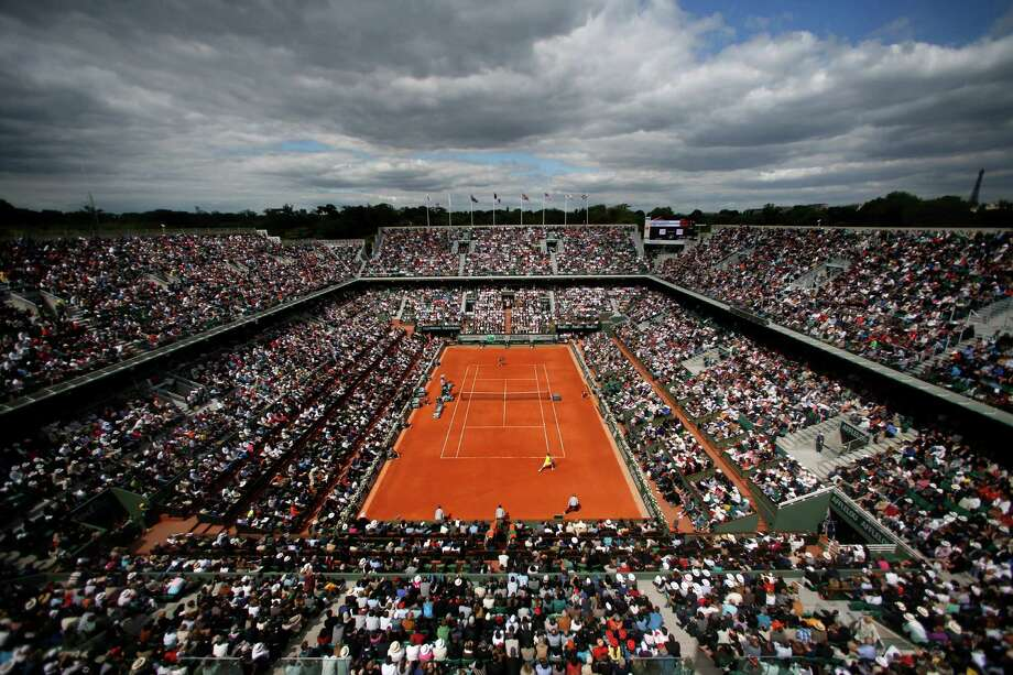 The crowd watches France's Jo-Wilfried Tsonga playing Serbia's Viktor Troicki, foreground, on center court during their fourth round match of the French Open tennis tournament at the Roland Garros stadium Sunday, June 2, 2013 in Paris. Photo: Petr David Josek, AP / AP