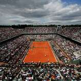 The crowd watches France's Jo-Wilfried Tsonga playing Serbia's Viktor Troicki, foreground, on center court during their fourth round match of the French Open tennis tournament at the Roland Garros stadium Sunday, June 2, 2013 in Paris.