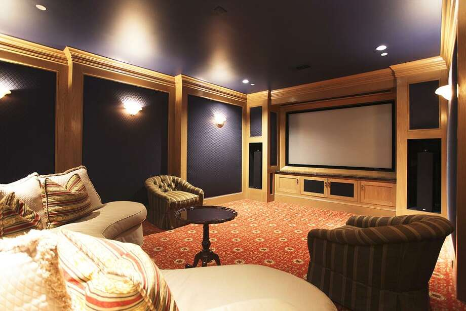 And for the full entertainment package, there is an impressive theater room with a drop-down projector TV with a 110 in screen, patterned wool carpet, padded fabric wall coverings, oak trim, and built-in theater style surround sound with components. Photo: HAR