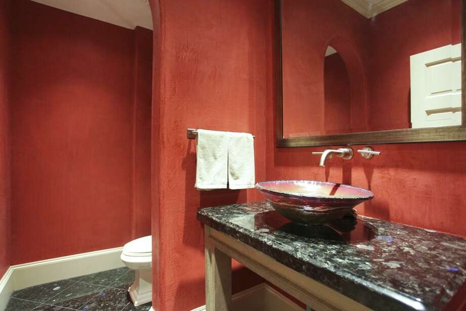 The upstairs powder room also welcomes the party with red Venetian plastered walls, Arctic Blue granite floors and counter, and an artisan glass vessel sink. This upstairs area of the home is also accessible by the built-in elevator. Photo: HAR