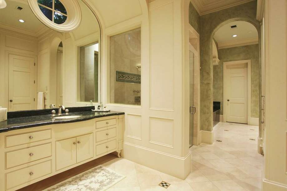 His bath is equally as impressive with paneled walls, separate vanity, a large walk-in shower with bench, a separate commode, marble floors and a huge walk-in closet with a window. Photo: HAR