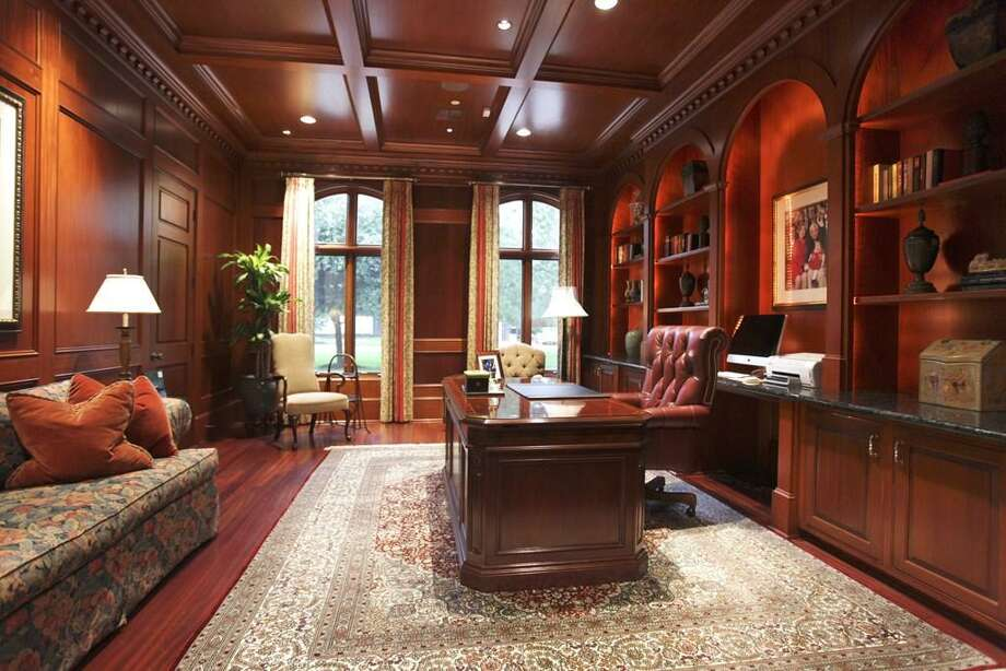 In front off the east gallery, you will experience a mahogany paneled library with mahogany coffered ceiling & moldings & Brazilian cherry floors. Recessed lighting accents the space with built-in bookshelves, cabinets & a granite counter credenza. Photo: HAR