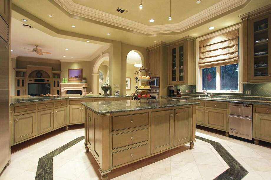 The kitchen also boasts a huge kitchen bar seating area, Tropical Forest granite counters, a tray ceiling, casement windows, glass front cabinets, plenty of additional cabinets throughout, an island work space and leather finished marble floors. Photo: HAR