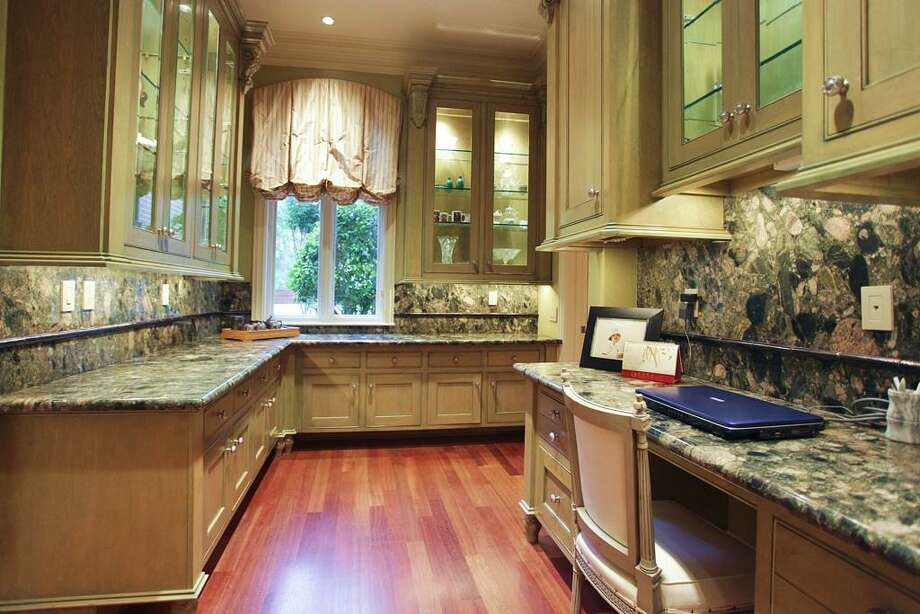 Adjoining the kitchen is the stunning butler's pantry complete with an enormous walk-in pantry, cabinets for every kind of service piece, lighted glass front cabinets, a small built-in office, Brazilian cherry floors & Brazilian granite counters. Photo: HAR