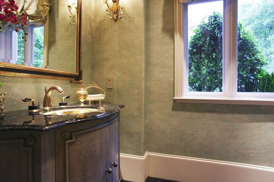 On the east side of the home off the foyer, you will find the downstairs powder room. Its an elegant space with Arctic Blue granite floors, silk paper wall coverings, and a China porcelain basin sunken into a furniture cabinet. Gorgeous! Photo: HAR