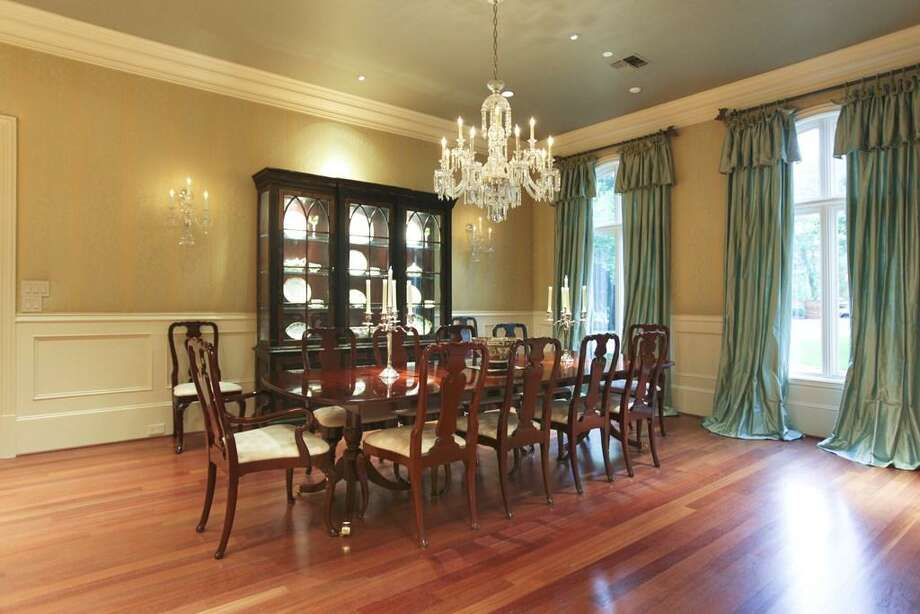 The dining space is complemented with custom art lighting, wall sconces, arched windows and padded fabric wall coverings. The room offers a simple elegance for fine dining. Photo: HAR