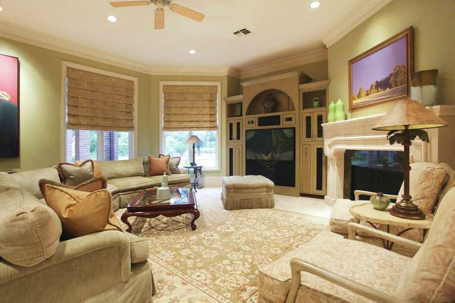 The family room includes a large stone wood burning fireplace, built-in entertainment center with surround sound, windows looking out to the pool patio, and leather finished marble floors. Photo: HAR
