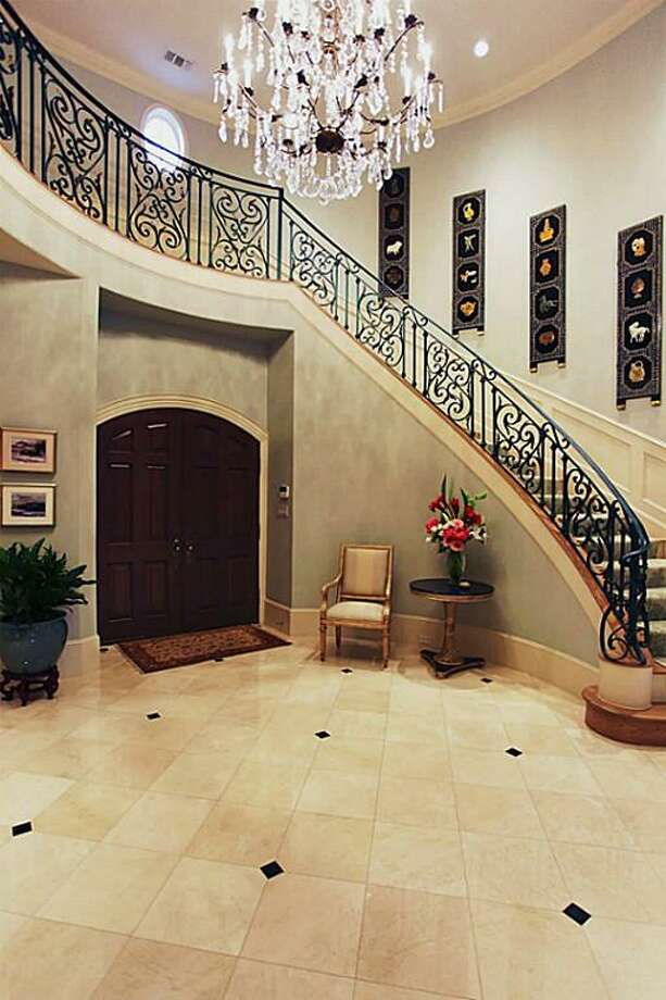 The foyer displays a grand staircase with an upper gallery and wrought iron railings. The 21 foot ceilings create a fantastic sense of space and the room is separated from the formal living room with square paneled columns. Photo: HAR