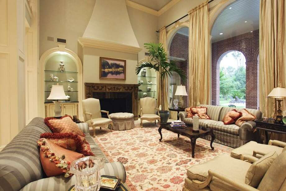 The formal living area boasts 21 ft ceilings with a wall of towering arched windows overlooking the lanai and pool patio. The massive fireplace flanked by arched built-ins along with 16 ft imported silk draperies, accentuate the height of the room. Photo: HAR