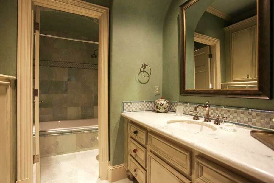 You will note each bedroom is en suite with its own uniquely designed bathroom. This full bath has a Caribbean green marble floor, decorative hardware, granite counters with light green highlights, mosaic tiling, and glass tile accents. Photo: HAR