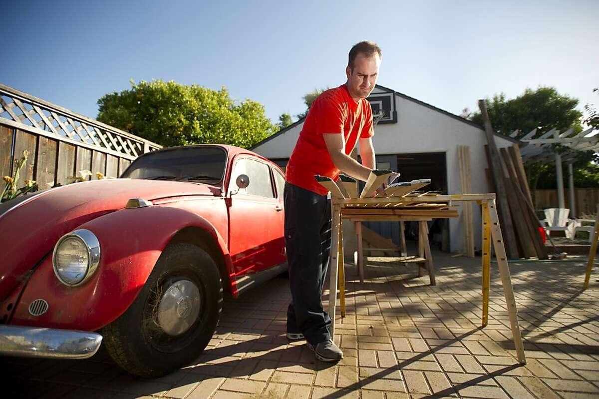 Chris Miller sands bedroom trim outside his Oakland, Calif., home on Thursday, May 15, 2013.