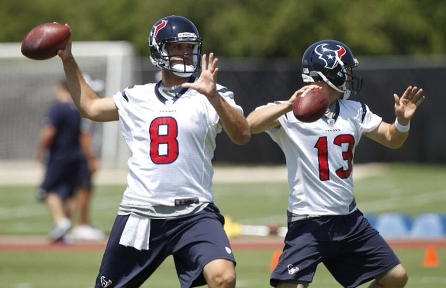 Texans quarterbacks Matt Schaub (8) and T.J. Yates (13) drop back to pass during Monday's OTAs at the Methodist Training Center.
