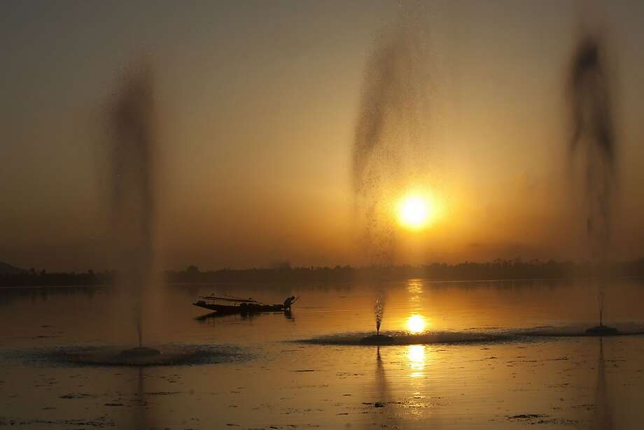 Beautiful Dal: A Kashmiri fisherman rows his boat past fountains on Dal Lake as the sun sets in Srinagar, India. Photo: Dar Yasin, Associated Press