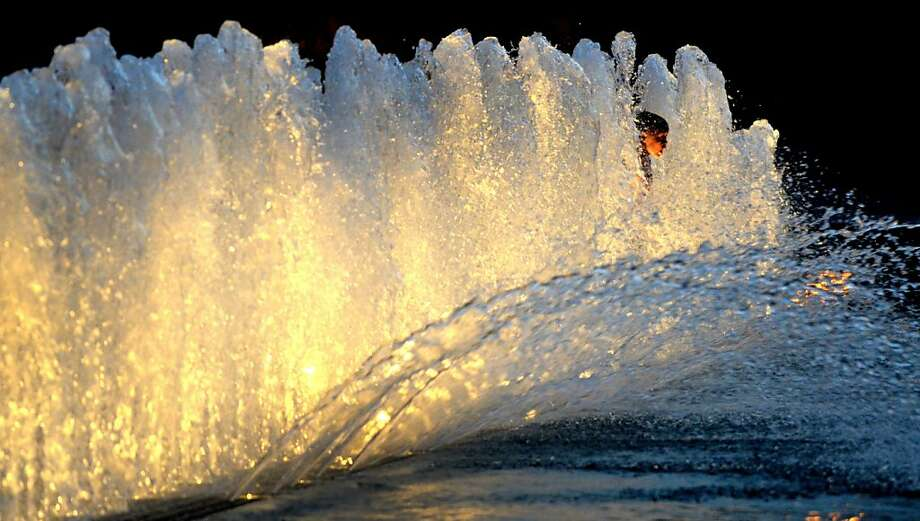Urban gusher:Seven-year-old Dakota Grant peeks through a wall of water while cooling off in the fountain at Clinton Square in Syracuse, N.Y. Photo: Kevin Rivoli, Associated Press
