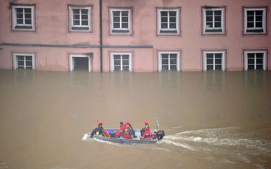 PASSAU, GERMANY - JUNE 03:  Rescue workers make their way with their boat through the flooded streets of the historic city center on June 3, 2013 in Passau, Germany. Heavy rains are pounding southern and eastern Germany, causing wide-spread flooding and ruining crops. At least two people are missing and feared dead in what is evolving into the most serious flood levels since the so-called 100-year flood of 2002. Portions of Austria and the Czech Republic are also inundated.  (Photo by Lennart Preiss/Getty Images) Photo: Lennart Preiss, Getty Images
