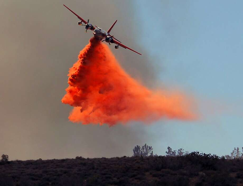 A plane drops fire retardant on a wildfire in Lancaster, Calif., Monday, June 3, 2013. Firefighters working in darkness doubled containment of a massive wildfire north of Los Angeles to 40 percent overnight, as cool, moist air moved in Monday to replace torrid weather. (AP Photo/Nick Ut) Photo: Nick Ut, Associated Press