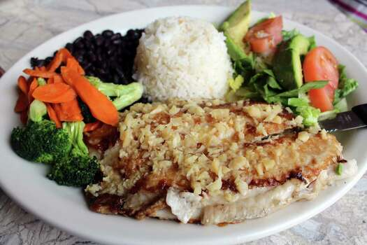 The Pescado al Mojo de Ajo at Viola's Ventanas comes with a filet of white fish grilled with garlic and lime marinade, served with Arroz Jardinero, choice of black, refried or charro beans and broccoli-carrot medley.  violasventanas.com Photo: Jennifer McInnis, San Antonio Express-News / San Antonio Express-News