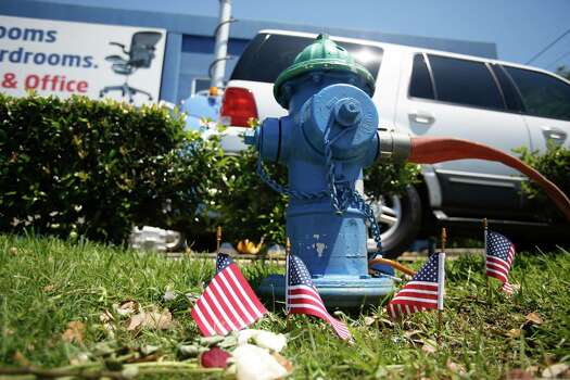 During the press conference, four flags are planted near a fire hydrant. Photo: Eric Kayne, For The Chronicle / © Eric Kayne 2013