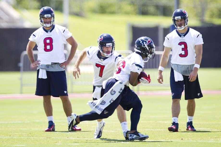 Texans quarterback Case Keenum (7) hands the ball off to running back Dennis Johnson (28) as quarterbacks Matt Schaub (8) and Stephen McGee (3) look on.