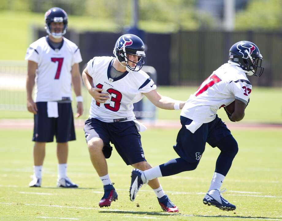 Texans quarterback T.J. Yates (13) hands the ball off to running back Ray Graham (37).