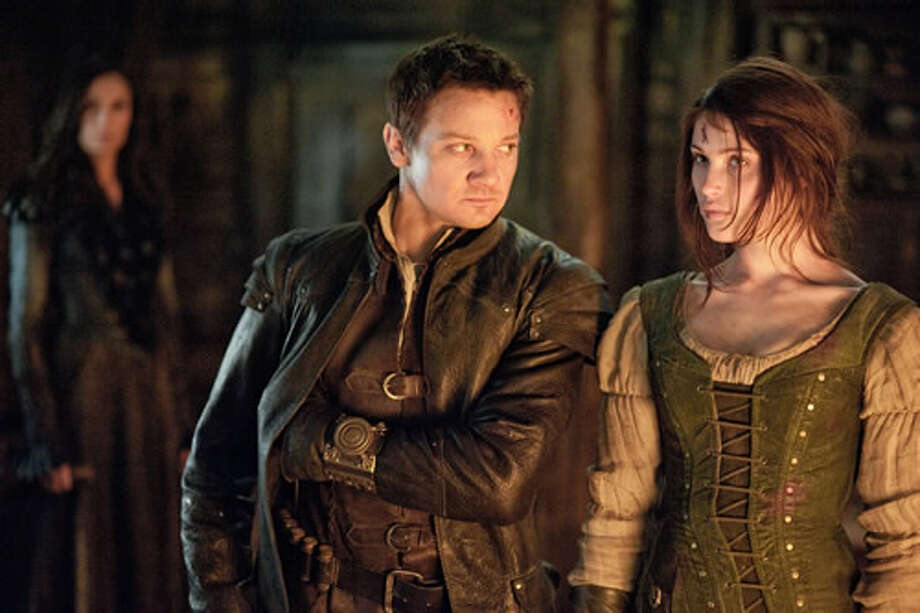 Famke Janssen as Muriel (background), Jeremy Renner as Hansel and Gemma Arterton as Gretel.