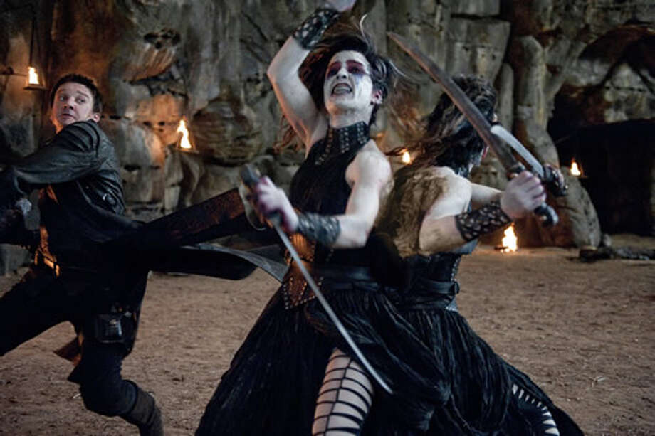 Jeremy Renner as Hansel battling a witch.
