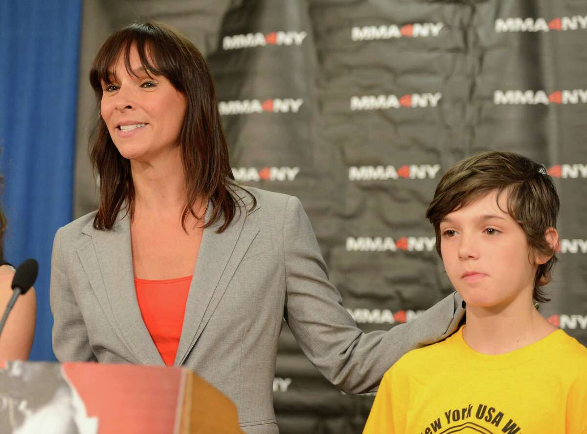 Jeniifer Bonjean, legal commentator and MMA enthusiast, introduces her son Dove during a press conference June 3, 2013, asking for the legalization of MMA by the state legislature in Albany, N.Y. Bonjean was joined by other advocates of the passage of the bill. (Skip Dickstien/Times Union)