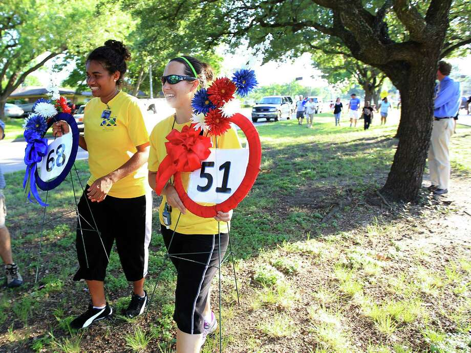 Missionaries Sister Susu, left, and Sister Jones, right, walk with wreaths as volunteers from the Sharpstown Civic Association placed blue and red ribbons along Bellaire Boulevard from Station 51 to I-59, Monday, June 3, 2013, in Houston, in remembrance of the four firefighters killed in Friday's fire. Photo: Karen Warren, Houston Chronicle / © 2013 Houston Chronicle