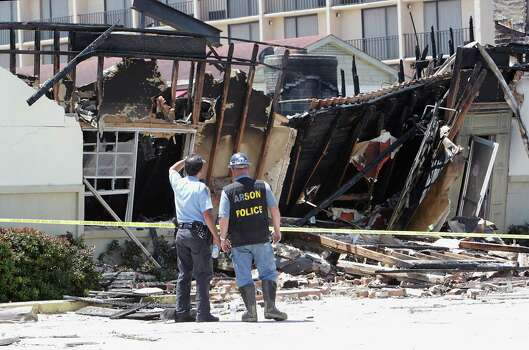 A police officer and an arson investigator Monday look over the remains of a motel fire in which four firefighters died. Photo: James Nielsen, Staff / © 2013  Houston Chronicle