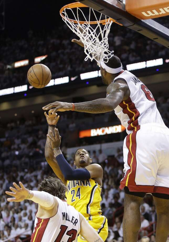 Miami Heat small forward LeBron James (6) blocks a shot to the basket by Indiana Pacers small forward Paul George (24) as Miami Heat shooting guard Mike Miller (13) falls to the court during the first half of Game 7 in their NBA basketball Eastern Conference finals playoff series, Monday, June 3, 2013 in Miami. (AP Photo/Lynne Sladky)