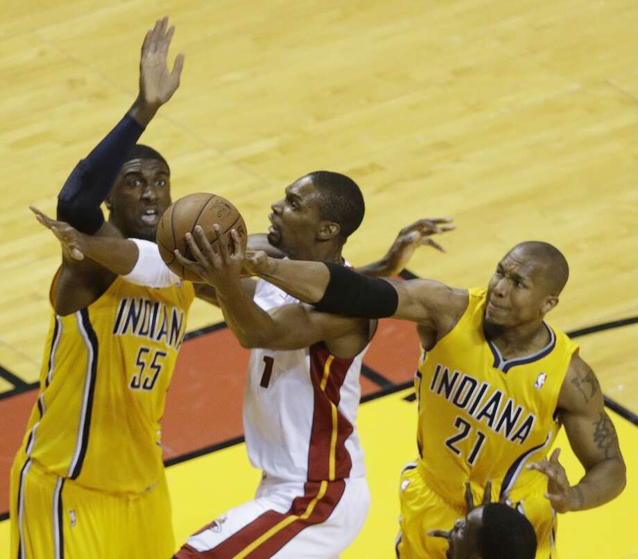 Miami Heat center Chris Bosh (1) heads to the hoop as Indiana Pacers power forward David West (21) and Indiana Pacers center Roy Hibbert (55) defend during the first half of Game 7 in their NBA basketball Eastern Conference finals playoff series, Monday, June 3, 2013 in Miami. (AP Photo/Wilfredo Lee)
