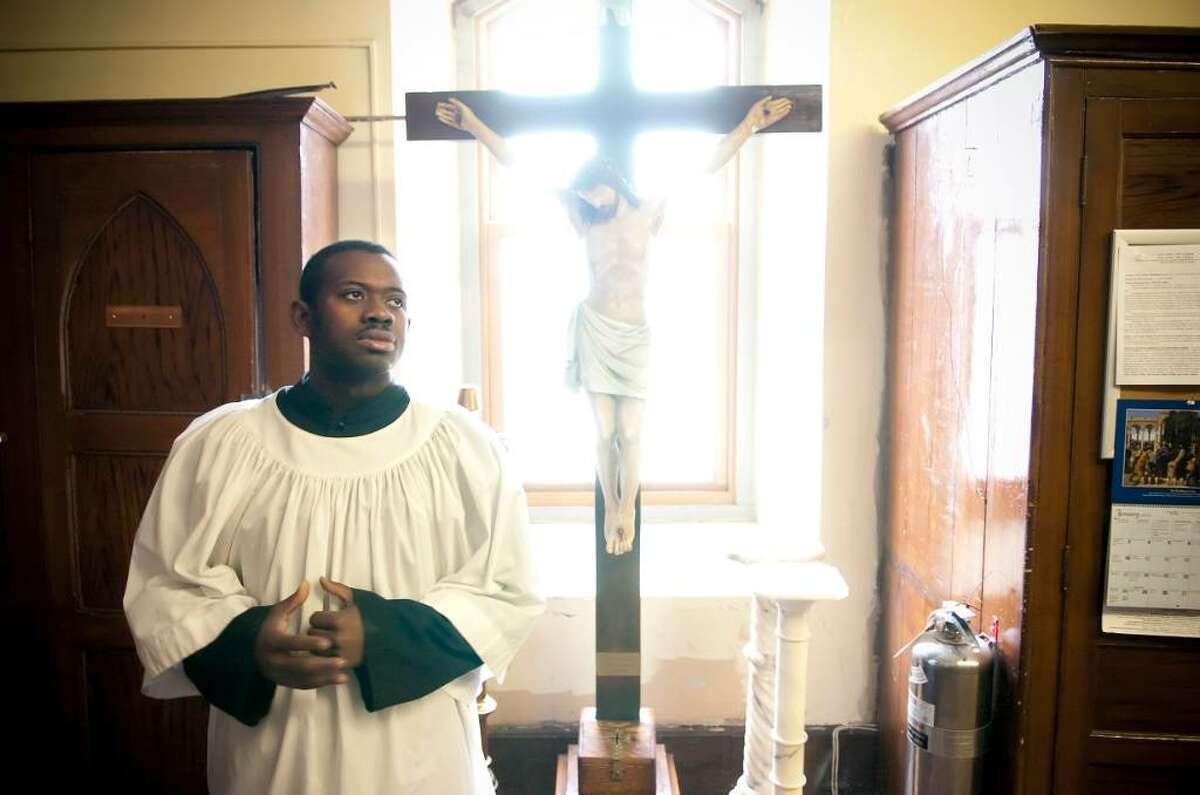 Altar server Ferry Galbert, a native of Haiti, prepares for a mass at St. John's Church in Stamford, Conn. dedicated the victims and survivors of yesterday's deadly earthquake in Haiti. Galbert has been able to reach some of his family members by phone but many others, including his grandmother have been unreacheable and their conditions are unknown.