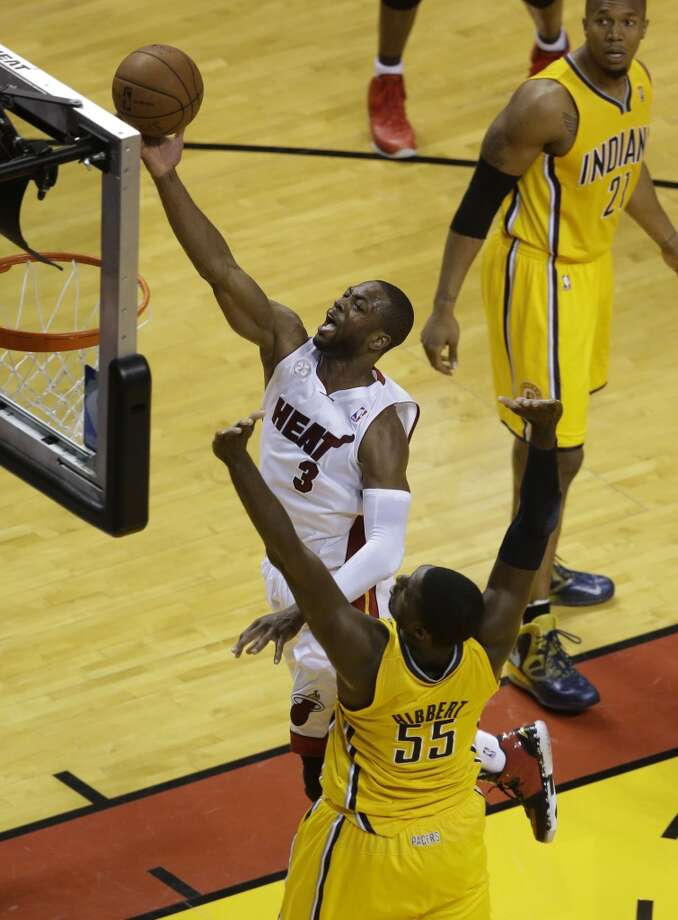 Miami Heat shooting guard Dwyane Wade (3) drives to the basket overIndiana Pacers center Roy Hibbert (55) during the first half of Game 7 in their NBA basketball Eastern Conference finals playoff series, Monday, June 3, 2013 in Miami. (AP Photo/Wilfredo Lee)