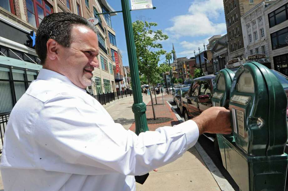 Steve Luccese of Pennsylvania puts quarters in a parking meter in front of Proctors Theater on State Street in Schenectady, N.Y., on Monday, June 3, 2013. There are efforts to raise the price of metered parking in the city of Schenectady. (Lori Van Buren / Times Union) Photo: Lori Van Buren / 00022672A