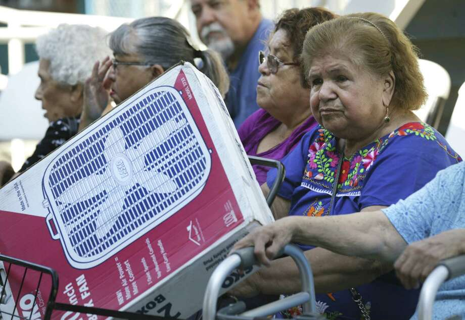 Tomasa Flores (right) and other Project Cool recipients rest after the St. Vincent de Paul fan distribution at Guadalupe Community Center. Photo: Bob Owen, San Antonio Express-News