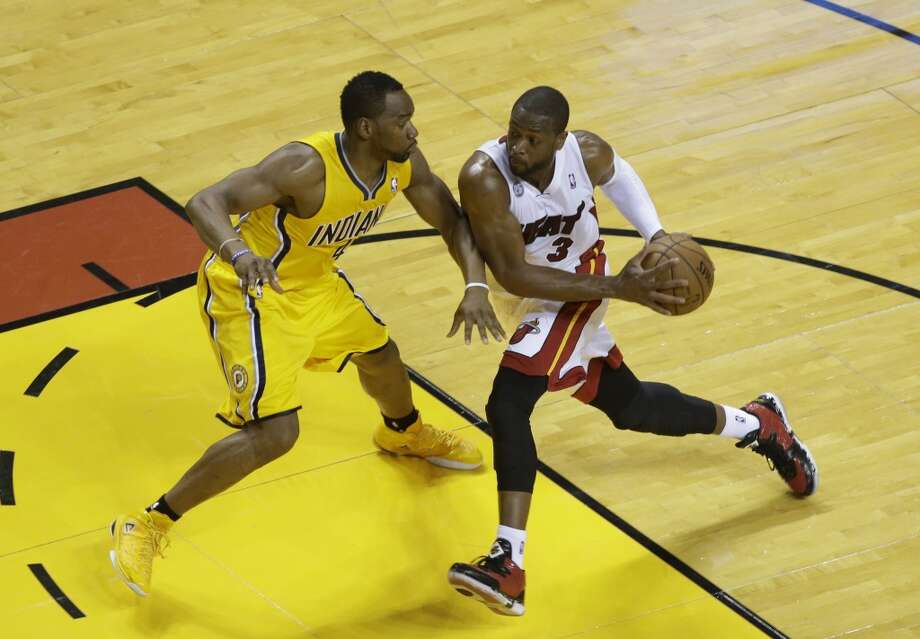 Miami Heat guard Dwyane Wade (3) dribbles the ball as Indiana Pacers forward Sam Young (4) during the first half of Game 7 in their NBA basketball Eastern Conference finals playoff series, Monday, June 3, 2013 in Miami. (AP Photo/Wilfredo Lee)