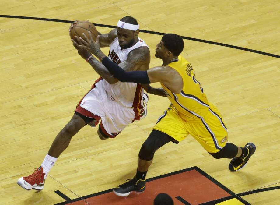 Miami Heat small forward LeBron James (6) dribbles the ball as Indiana Pacers small forward Paul George (24) defends during the first half of Game 7 in their NBA basketball Eastern Conference finals playoff series, Monday, June 3, 2013 in Miami. (AP Photo/Wilfredo Lee)
