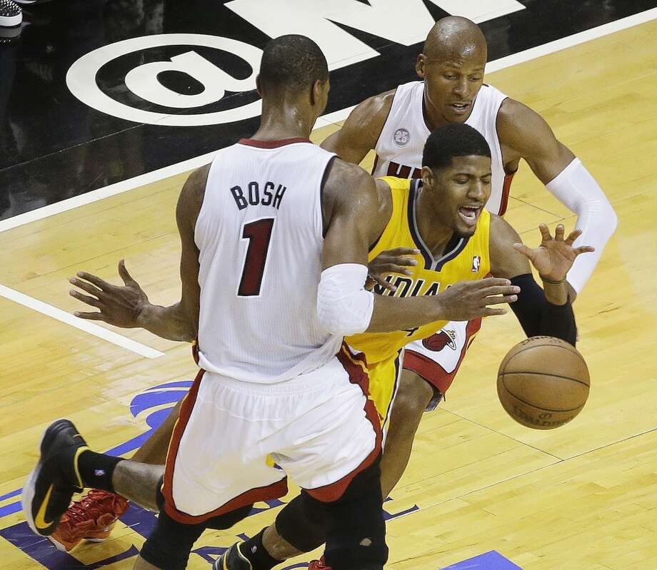Miami Heat shooting guard Ray Allen (34) and Miami Heat center Chris Bosh (1) defend Indiana Pacers small forward Paul George (24) during the first half of Game 7 in their NBA basketball Eastern Conference finals playoff series, Monday, June 3, 2013 in Miami. (AP Photo/Wilfredo Lee)