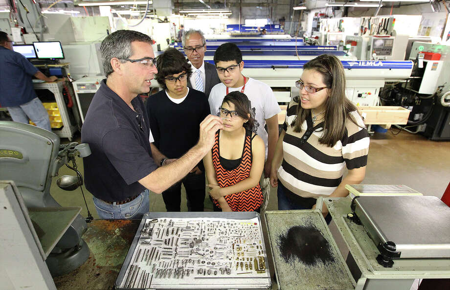 Vice president of Cox Manufacturing Michael Petrusch (left) shows freshman students Antonio Orta (second from left), Devon Ortega, Cristal Otero and Jeanette Platt from South San High School examples of some of the parts the facility fabricates during a tour of Cox Manufacturing on Monday, May 20, 2013. Through a non-profit program called Motivate Our Students, 19 freshmen were shown what educational skills are required for today's workforce. Petrusch stressed that math was critical for students to learn and to appreciate as they continued with school. At the end of the tour, the students received a brass whistle made at the facility as a memento of their visit. (Kin Man Hui/San Antonio Express-News) Photo: San Antonio Express-News / © 2013 San Antonio Express-News