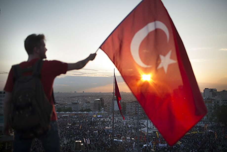 ISTANBUL, TURKEY - JUNE 03:   A protestor waves the Turkish flag from a roof top at Taksim square on June 3, 2013 in Istanbul, Turkey. The protests began initially over the fate of Taksim Gezi Park, one of the last significant green spaces in the center of the city. The heavy-handed viewed response of the police, Prime Minister Recep Tayyip Erdogan and his government's increasingly authoritarian agenda has broadened the rage of the clashes. (Photo by Uriel Sinai/Getty Images)    ***BESTPIX*** Photo: Uriel Sinai, Getty Images